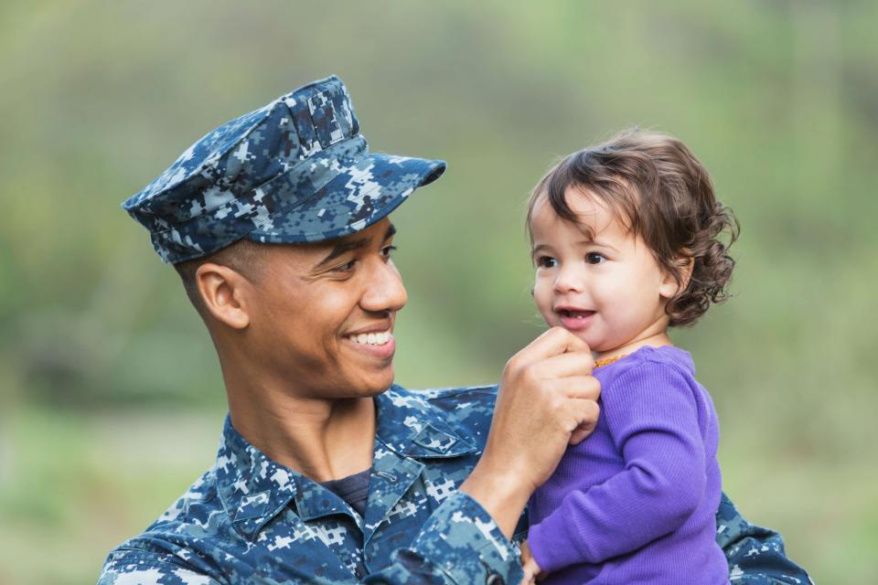 military father holding toddler girl