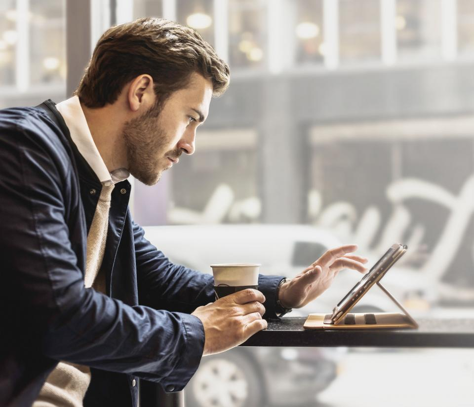 Man using a tablet to do online banking in a coffee shop