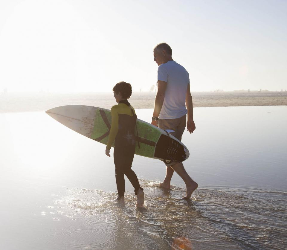 Father and young son with surf board walking on beach