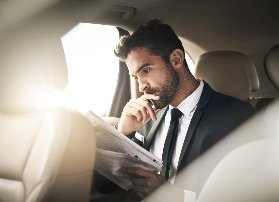 business owner reading the paper in a car