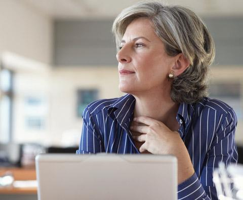 Woman at computer thinking about investing